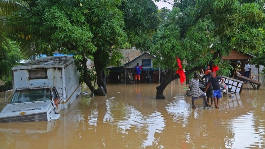 Oct. 26, 2012: Residents of Leogane, Haiti find higher ground as the water level continues to rise.  Residents of Leogane have had five consecutive days of rain in the aftermath of Hurricane Sandy, which caused serious flooding and claimed at least 26 lives in the impoverished country.