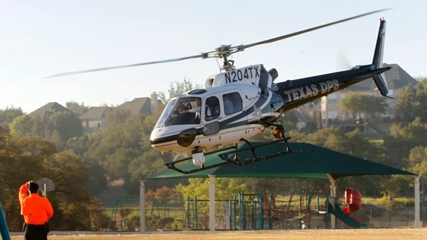 AUSTIN, TX - SEPTEMBER 6:  Republican presidential candidate and Texas Gov. Rick Perry takes off aboard a Texas Department of Public Safety helicopter for an aerial tour of the area around Steiner Ranch where homes were destroyed by wildfires the last two days September 6, 2011 in Austin, Texas. Perry, who left his presidential campaign to respond to the fires, said more than 1,000 houses in the area were destroyed. (Photo by Erich Schlegel/Getty Images)