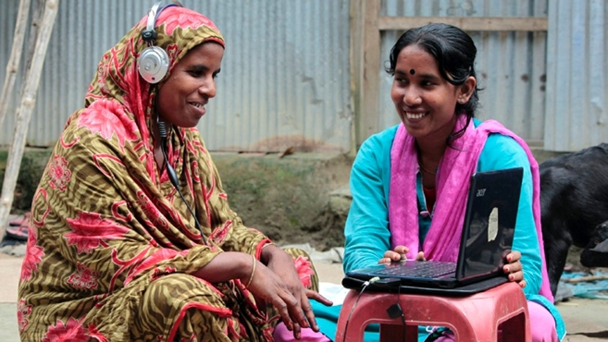 Sept. 30, 2012: Bangladeshi Info Lady Mehedi Akthar Misty, right, helps Amina Begum, 45, to talk with her husband via Skype in a remote impoverished farming village in Bangladesh.