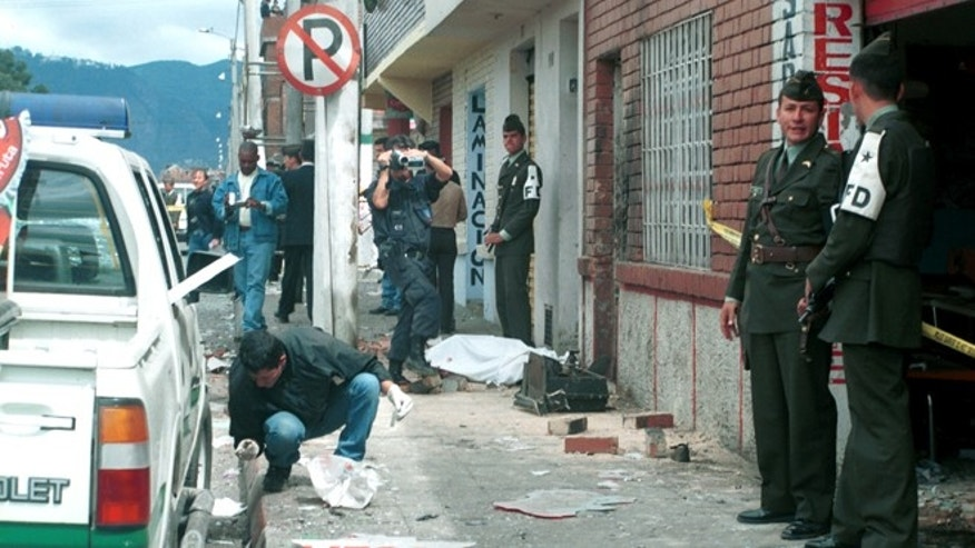 400154 01: Police investigate a bicycle bombing in front of a police precinct January 25, 2002 in Bogota, Colombia. Three police officers and at least four civilians were killed in the attack. A victim lies on a sidewalk in the background. Four more bicycle bombs were found in front of other police precincts were deactivated before any further damage could take place. No one claimed responsability for the terrorist attack. (Photo by Carlos Villalon/Getty Images)