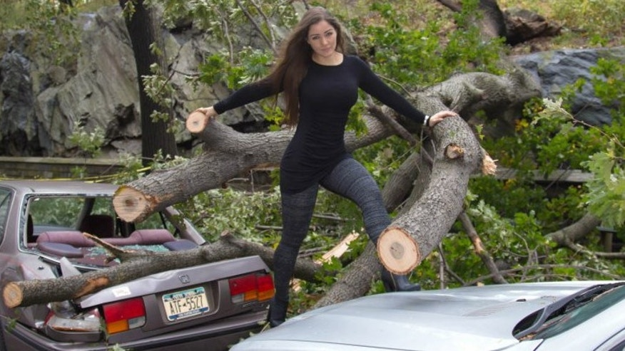 Nana Gouvêa poses on top of a crushed car in Manhattan after Superstorm Sandy wrecks havoc in the city.