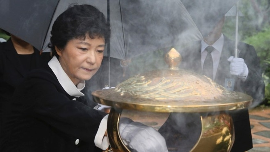 Aug. 21, 2012: In this file photo, Park Geun-hye, presidential candidate of the ruling Saenuri Party, burns incense in front of the tomb of her father and former authoritarian President Park Chung-hee at National Cemetery in Seoul, South Korea.