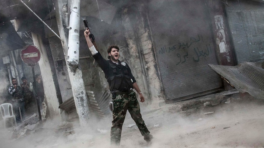 Nov. 04, 2012: A rebel fighter claims for victory after he fires a shoulder-fired missile toward a building where Syrian troops loyal to President Bashar Assad are hiding while they attempt to gain terrain against the rebels during heavy clashes in the Jedida district of Aleppo, Syria.