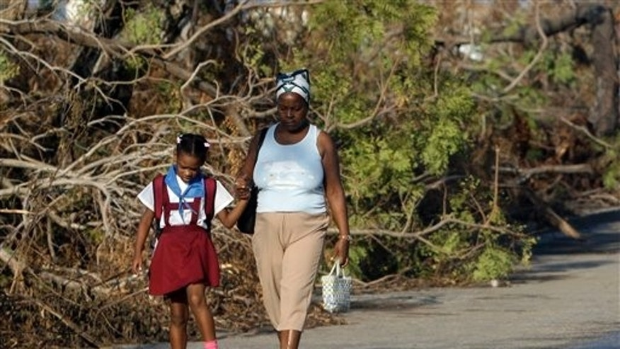 A student walks to school past trees that fell during the passing of Hurricane Sandy in Santiago de Cuba.