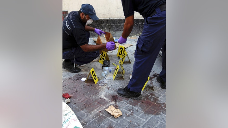 Monday, Nov. 5, 2012 -  Police collect evidence at the scene of an explosion that killed an Asian man in Manama, Bahrain.