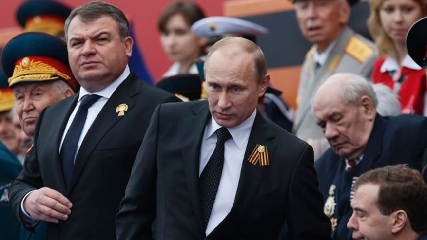 May 9, 2012: In this file photo, Russia's Defense Minister Anatoly Serdyukov, left, Russian President Vladimir Putin, center, and Prime Minister Dmitry Medvedev, bottom right, watch the Victory Day Parade, in Moscow.
