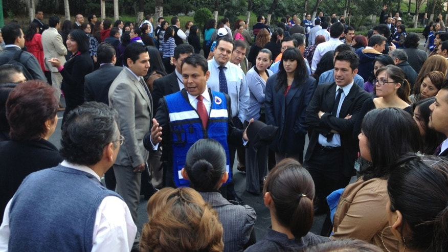 Nov. 7, 2012: People who work in office buildings along El Paseo de la Reforma listen to instructions after evacuating their offices in Mexico City on Wednesday.