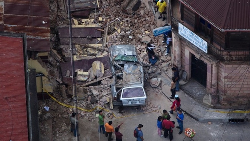Nov. 7, 2012: Residents walk among rubble after a magnitude 7.4 earthquake struck in San Marcos, Guatemala.
