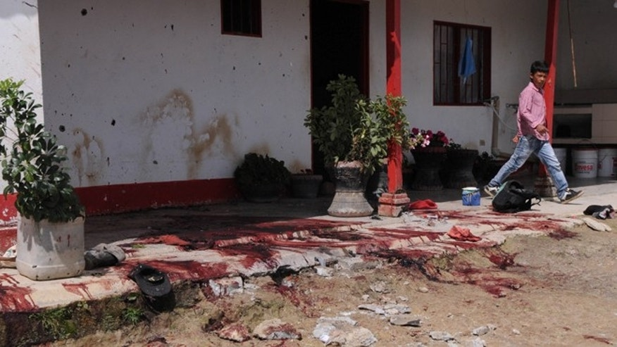 Nov. 8, 2012: Blood covers the front patio of a farmhouse where 10 laborers were killed in Santa Rosa de Osos in Colombia&#39&#x3b;s Antioquia state.