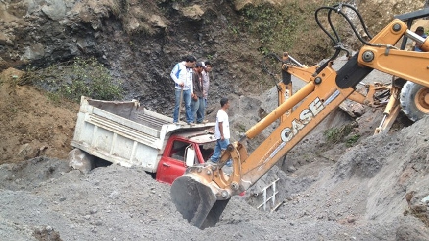 Nov. 7, 2012: Residents use heavy equipment to look for people feared buried at a sand mine, after a magnitude 7.4 earthquake struck in San Marcos, Guatemala.