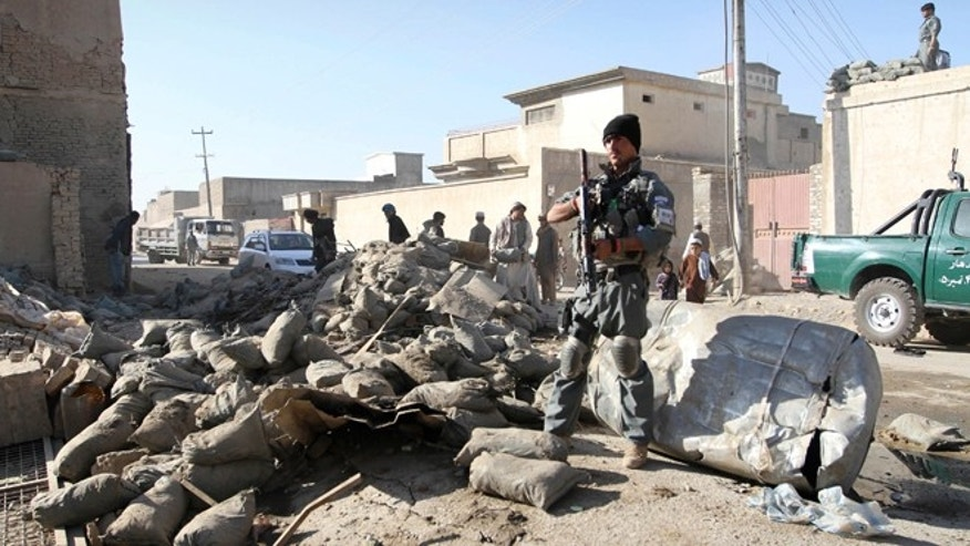 Nov. 8, 2012: An Afghan policeman stands guard at the scene of a suicide attack in Kandahar, south of Kabul, Afghanistan.
