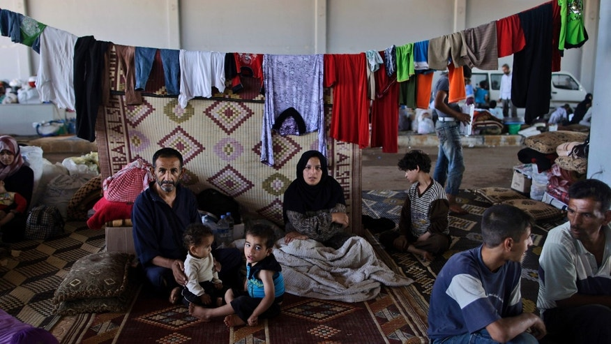 Sept. 13, 2012: In this file photo, a Syrian family, who fled their home due to government shelling, take refuge at Bab Al-Salameh crossing border, hoping to cross to one of the refugee camps in Turkey, near the Syrian town of Azaz.