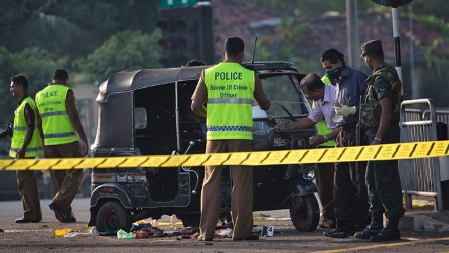 Nov. 10, 2012: Police forensic officers examine a bullet-ridden three-wheeled vehicle used by inmates for their unsuccessful escape attempt, close to the entrance of a prison in Colombo, Sri Lanka.