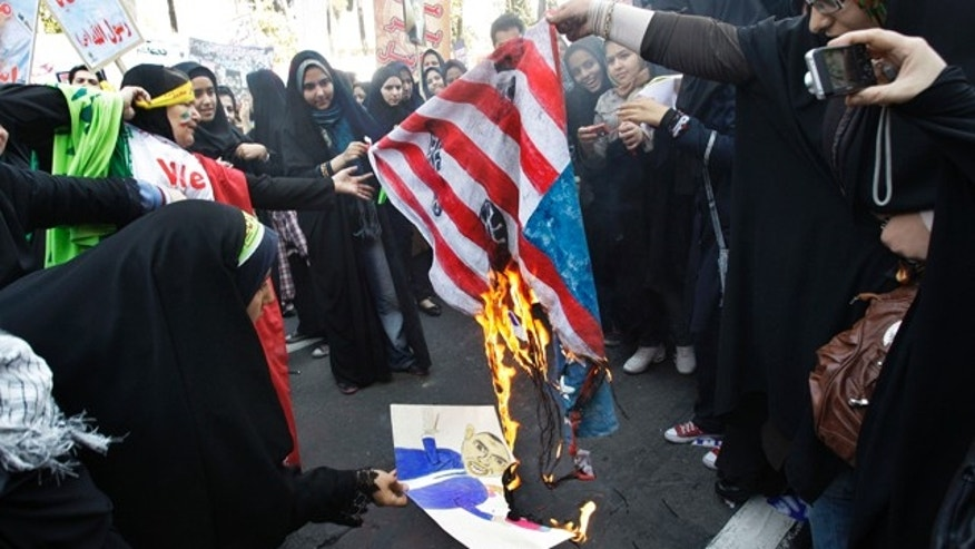 Nov. 2, 2012: Iranian demonstrators burn a representation of a U.S. flag and a caricature of President Barack Obama, in an annual state-backed rally in front of the former US Embassy in Tehran. (AP)