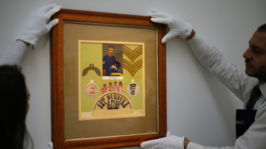 Nov. 9, 2012: Employees from Sotheby's auction house adjust the original Sir Peter Blake 1967 collage for the iconic Beatles album Sgt Pepper's Lonely Hearts Club Band, which will be sold at  auction, during a press viewing in London.