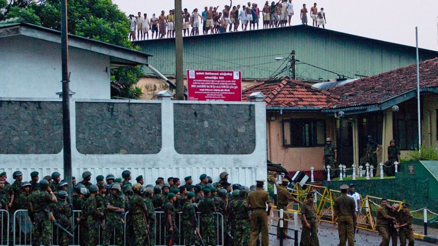 Nov. 9, 2012: Sri Lankan inmates shout from a roof of a prison building as prison guards assist an injured colleague, foreground right, outside a prison in Colombo, Sri Lanka.