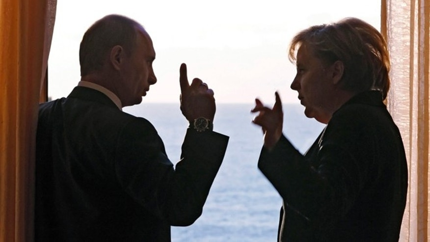 In this Sunday, Jan. 21, 2007 pool file photo German Chancellor Angela Merkel and Russian President Vladimir Putin speak during their meeting in Putin's residence in the Russian Black Sea resort of Sochi.