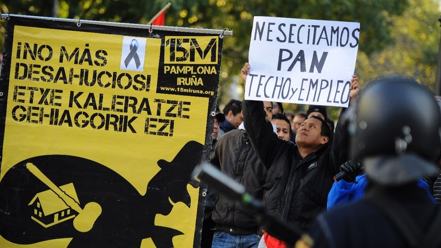 Nov. 14, 2012: A man who identified himself as Edwin, 32, from Ecuador, right, who was evicted from his home over debts,  holds up banner reading ''We need bread, roof and employment''  beside a poster to support people fighting against evictions reading, ''No More Evictions'', in front of Spanish riot police during a general strike against government austerity measures, in Pamplona, northern Spain.
