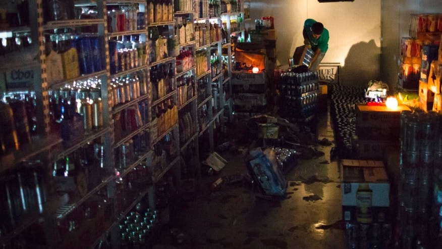 A worker cleans out a walk-in refrigerator in the dark at the West Side Wine Liquor store, in  Hoboken, New Jersey.
