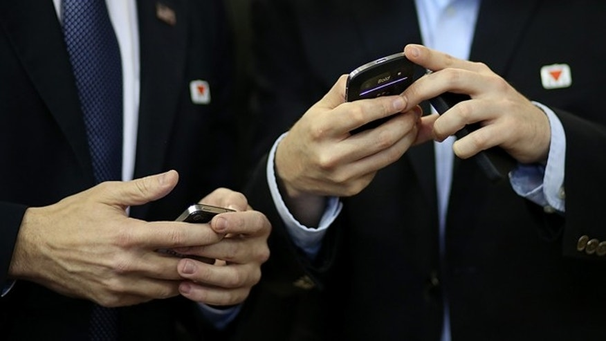 AVON LAKE, OH - OCTOBER 29:  Campaign staffers for Republican presidential candidate, former Massachusetts Gov. Mitt Romney check their smartphones during a campaign rally at Avon Lake High School on October 29, 2012 in Avon Lake, Ohio. Romney canceled campaign events on October 29 and 30 due to Hurricane Sandy.  (Photo by Justin Sullivan/Getty Images)