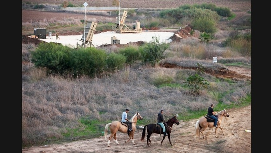 Nov. 18, 2012: Israelis ride their horses next to a military Iron Dome defense missile system.