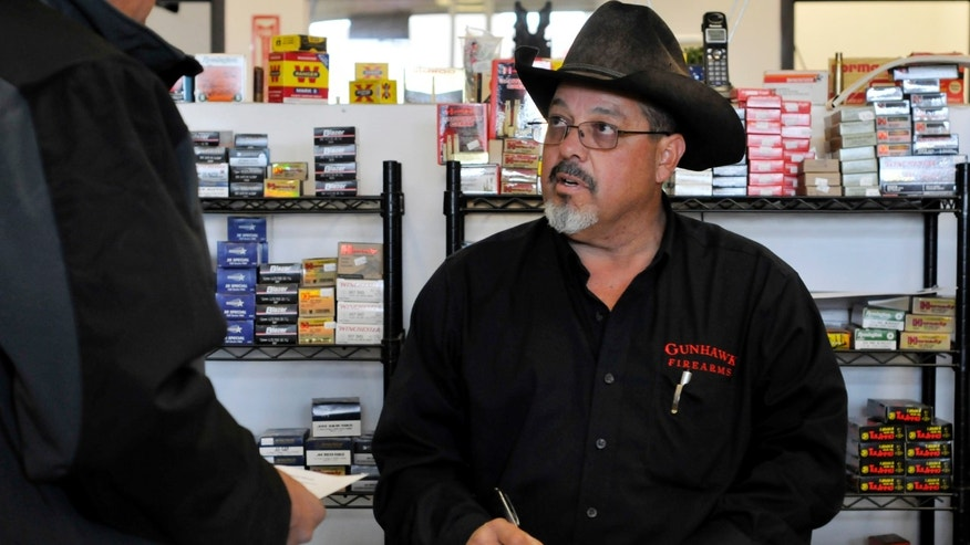 In this Saturday, Nov. 10, 2012 photo, store owner Mark Chavez, right, signs up a Belen rancher for the Gunhawk Firearms coyote hunt in Los Lunas, N.M. Chavez, who has faced two weeks of angry phone calls and protests - and even a threat to his life. (AP Photo/Albuquerque Journal, Marla Brose)