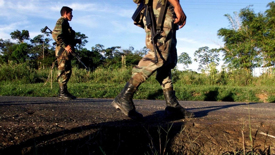 CAQUETA, COLOMBIA - JULY 31:  Colombian soldiers patrol the highway that leads to San Vicente del Caguan from their base in Caqueta, Colombia on July 31, 2002. Despite a strong military presence in the former demilitarized zone, FARC guerrillas still maintain their control over the territories. (Photo by Carlos Villalon/Getty Images.)