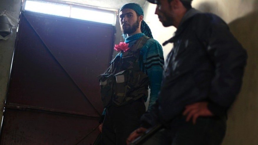 Nov. 17, 2012: Two Syrian fighters, one wearing a flower in his vest, take part in clashes with Syrian army forces in the town of Harem, on the outskirts of Idlib, Syria.