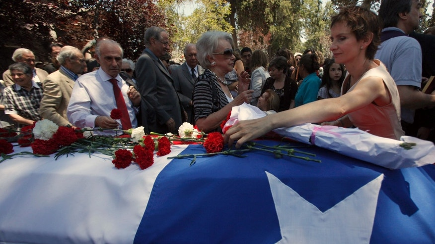 Mayor-elect of Santiago, Carolina Toha, places flowers on the flag draped casket of her father Jose Toha during his reburial in Santiago, Chile, Monday, Nov. 19, 2012. (AP Photo/Luis Hidalgo)