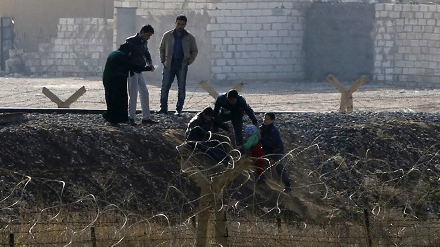 Nov. 21: Syrian refugees try to cross the border fence from the northern Syrian town of Ras al-Ain into Turkey.