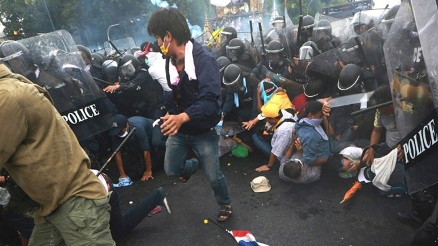 Nov. 24, 2012: Anti-government protesters try to flee from tear gas fired by police in Bangkok.