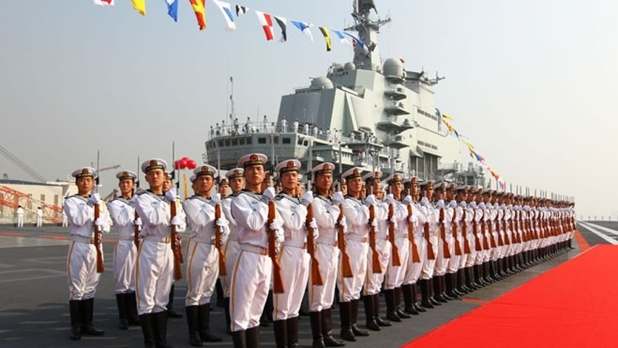 "Sept. 25, 2012: Military officers stand onboard China's aircraft carrier ""Liaoning"" in Dalian, northeast China's Liaoning Province, as the country formally entered its first aircraft carrier into service."