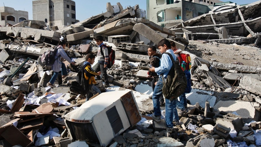Nov. 26, 2012 - Palestinian school children walk in the rubble left days after an Israeli strike destroyed the Hamas interior ministry in Gaza City.