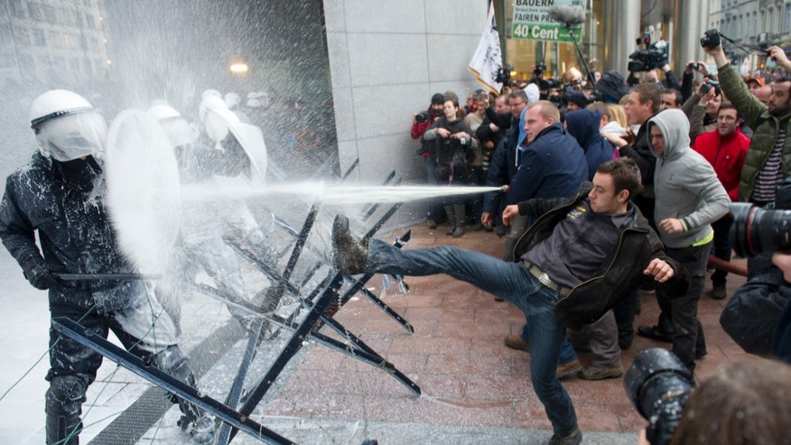 Nov. 26, 2012 - Police officers sprayed with milk by European milk farmers during a demonstration outside the European Parliament in Brussels.