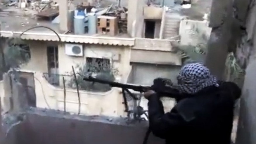 Nov. 27, 2012: In this image taken from video obtained from the Shaam News Network, which has been authenticated based on its contents and other AP reporting, a Syrian rebel fires his weapon during clashes with government forces in Aleppo, Syria.