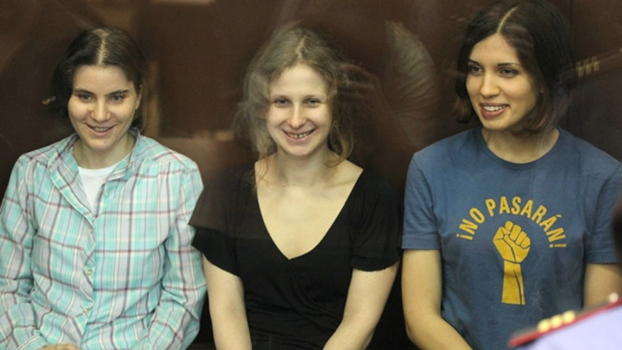 Aug. 17, 2012: Nadezhda Tolokonnikova, right, Yekaterina Samutsevich, left, and Maria Alekhina, center, members of feminist punk group Pussy Riot seen behind a glass wall at a court in Moscow, Russia.
