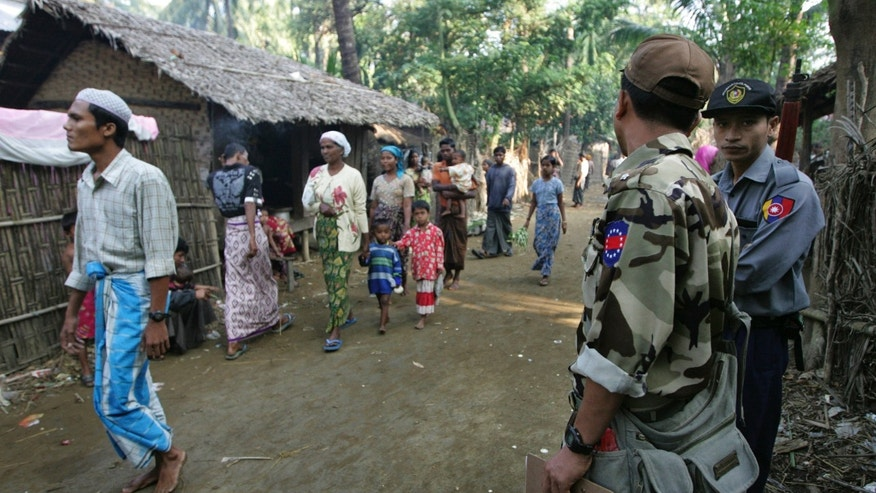 Nov. 10, 2012: In this photo, Muslim refugees walk as Burma police officers stand guard at Sin Thet Maw relief camp in Pauktaw township, Rakhine state, western Burma.