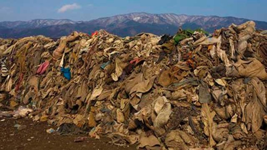 FILE - Clothing lie in heaps at the site of a neighborhood destroyed by the 2011 earthquake and tsunami, in Rikuzentakata, Japan.