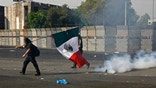 "A demonstrator carrying a Mexican national flag walks past a cloud of tear gas during clashes with police outside the National Congress, just hours before Mexico's new president was to take the oath of office in Mexico City, Saturday, Dec. 1, 2012.  Hundreds of protesters  opposed to newly sworn-in President Enrique Pena Nieto banged on the steel security barriers around Congress, threw rocks, bottle rockets and firecrackers at police and yelled ""Mexico without PRI!""  Pena Nieto took power at midnight in a symbolic ceremony and formally took the oath of office Saturday morning in congressional chambers. (AP Photo/Marco Ugarte)"