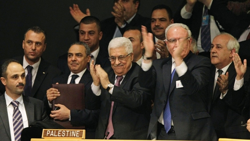 Nov. 29, 2012: Members of the Palestinian delegation react as they surround Palestinian President Mahmoud Abbas, center, applauding, during a meeting of the United Nations General Assembly after a vote on a resolution on the issue of upgrading the Palestinian Authority's status to non-member observer state passed in the United Nations in New York.