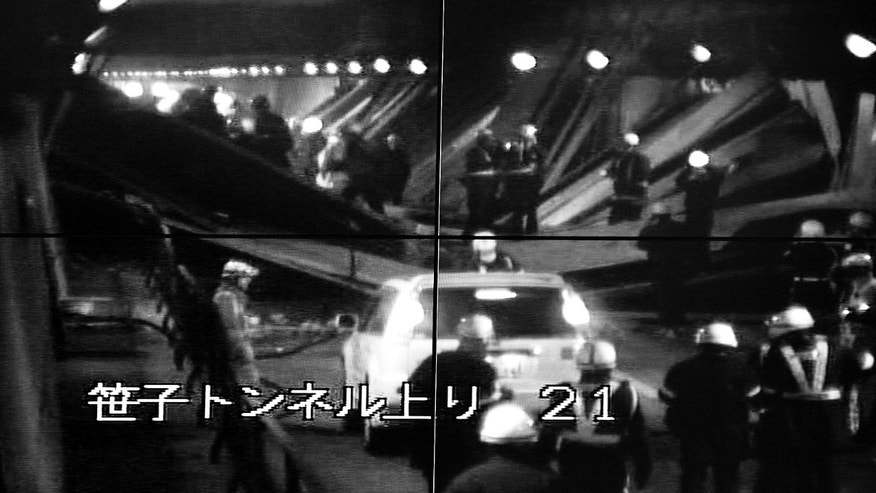 Dec. 2, 2012 - Image taken from monitoring camera of Central Nippon Expressway, Tokyo, showing rescuers looking for the injured among fallen roof panels in the Sasago Tunnel.