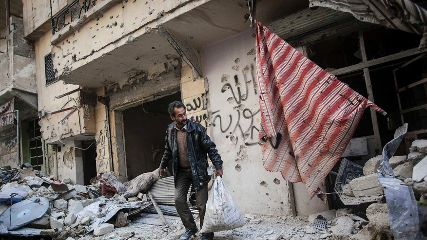 Dec. 2, 2012: In this photo, a man collects his belongings after his home was damaged due to heavy fighting between Free Syrian Army fighters and government forces in Aleppo, Syria.