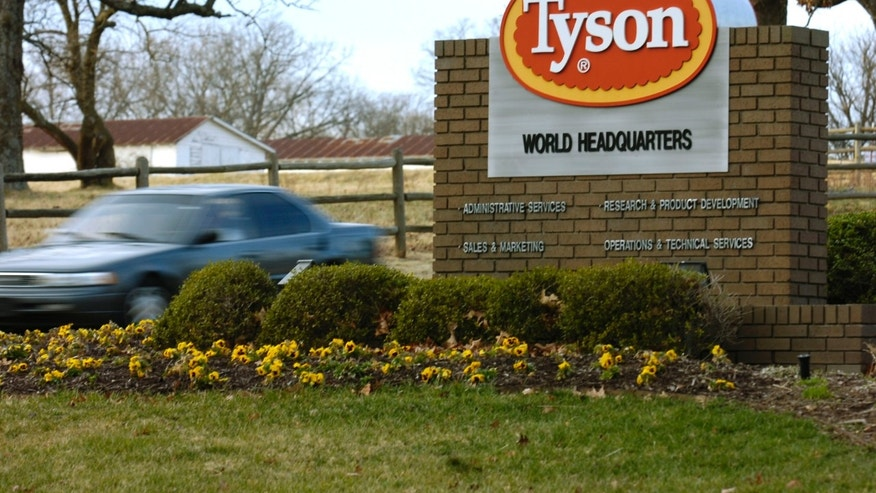 FILE - In this Jan. 29, 2006, file photo, a car passes in front of a Tyson Foods Inc., sign at Tyson headquarters in Springdale, Ark.  A chlorine gas leak that sickened nearly 200 people at a Tyson Foods plant in Arkansas last year happened because a worker who couldn't read the English-language label on a barrel of chemicals inadvertently poured bleach into it, the Centers for Disease Control and Prevention said in a report released Thursday. (AP Photo/April L. Brown, File)