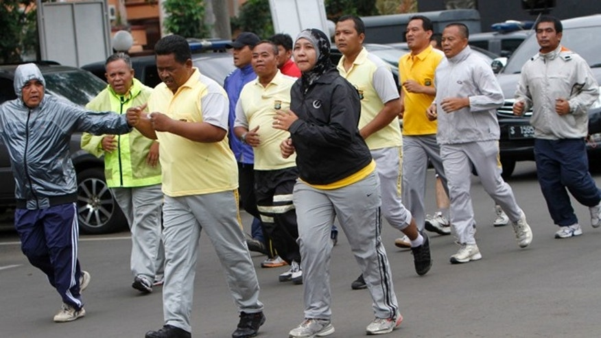 In this photo taken Dec. 4, 2012, plain-clothes Indonesian police officers do exercise during a new diet program for police in Tangerang, outskirts of Jakarta, Indonesia.