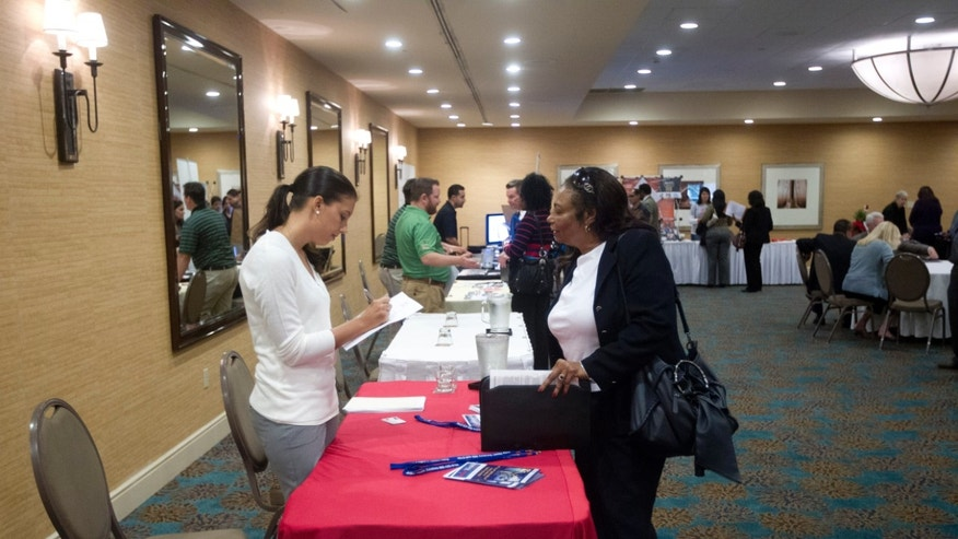 A woman fills out an application at the Fort Lauderdale Career Fair, in Dania Beach, Fla.