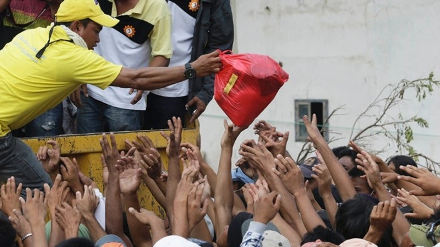 Dec. 9, 2012: Residents affected by typhoon Bopha crowd as relief goods are distributed at New Bataan township, Compostela Valley in southern Philippines.