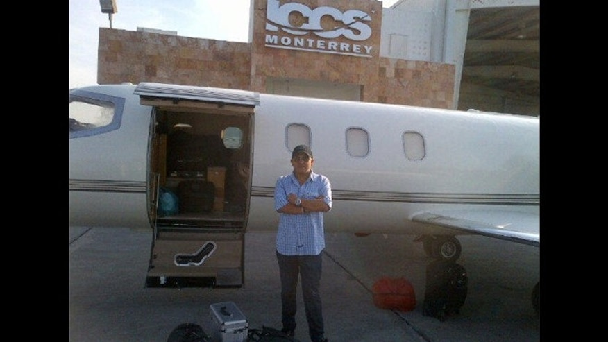 Jenni Rivera's publicist Arturo Rivera (unrelated) stands in front of what is believed to be the Learjet 25 aircraft that crashed on Sunday morning. The  photo was posted on Arturo's Twitter account on December 8th in Monterrey, Mexico.
