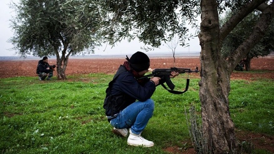Dec. 10, 2012: Free Syrian Army fighters aim their weapons, close to a military base, near Azaz, Syria.