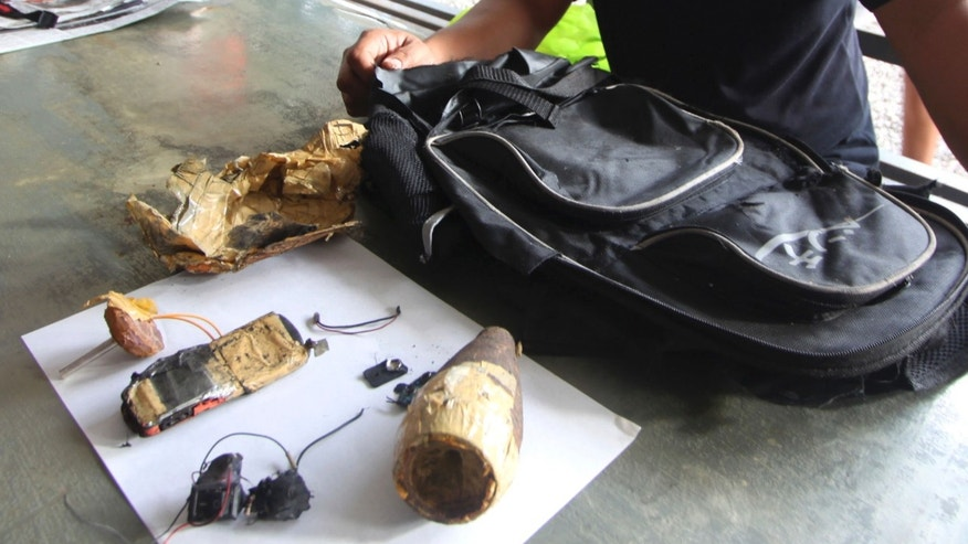 A Philippine National Police investigator reveals an improvised explosive device (IED) from a backpack which a Malaysian member of a terrorist group Jemaah Islamiya was trying to detonate Friday in Davao city in southern Philippines, Saturday Dec. 15, 2012. A suspected terrorist, identified as Mohd Noor Fikrie Bin Abd Kahar, was fatally shot by police late Friday following a scuffle inside a hotel where he and his Filipino wife had checked in, Davao city police chief Ronald de la Rosa said. (AP Photo/Karlos Manlupig)