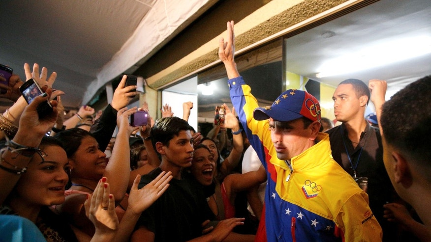 Miranda State's Gov. Henrique Capriles, right, greets his supporters after being re-elected during an elections in Caracas, Venezuela, Sunday, Dec. 16, 2012. Capriles lost to Chavez in the country's October election, and his re-election Sunday will allow him to cement his position as Venezuela's dominant opposition leader, even as other opposition candidates floundered. (AP Photo/Fernando Llano)